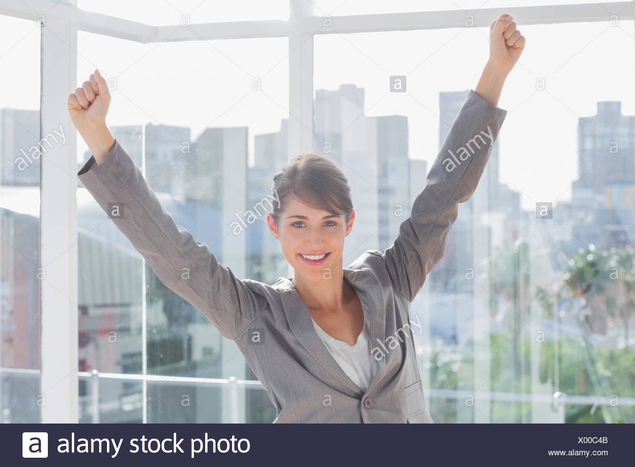 Excited businesswoman cheering and smiling - Stock Image
