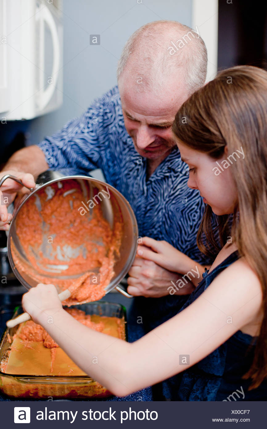 Father and daughter cooking together - Stock Image