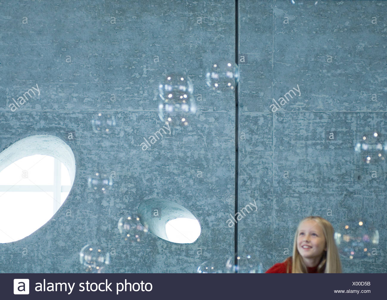 Girl looking at bubbles - Stock Image