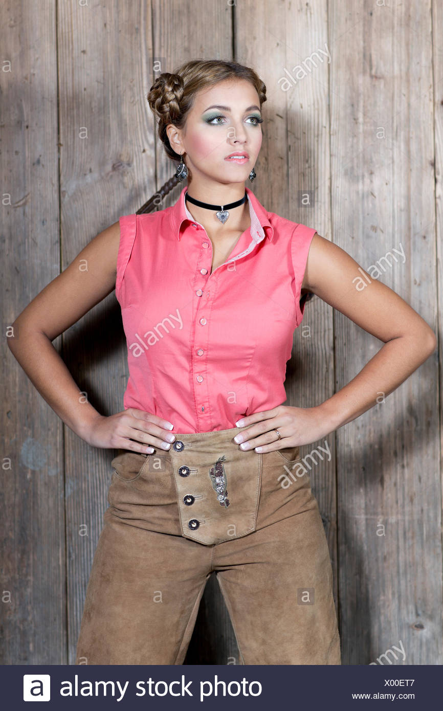 Young woman wearing a pink sleeveless top and traditional leather pants, dirndl look - Stock Image
