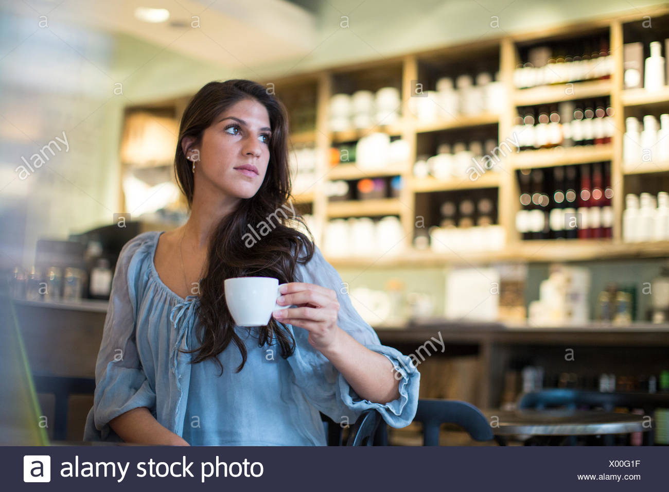 Young woman sitting in cafe looking sideways - Stock Image