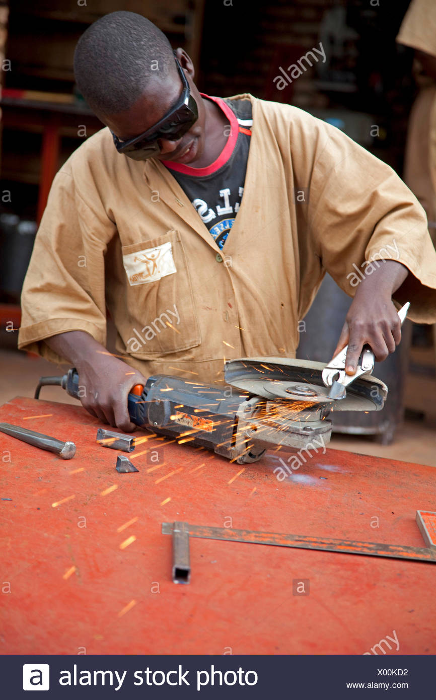 teenager working with angle grinder in a workshop of an aid organisation, Burundi, Ngozi - Stock Image
