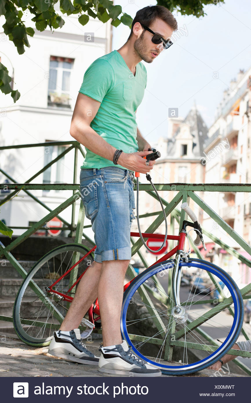 Man holding a lock for locking his bicycle, Paris, Ile-de-France, France - Stock Image