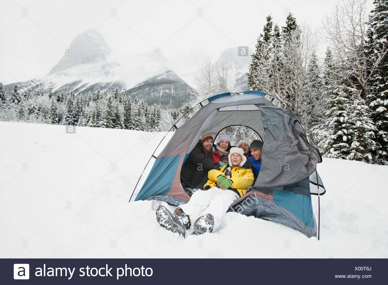 young adults enjoying winter camping - Stock Image