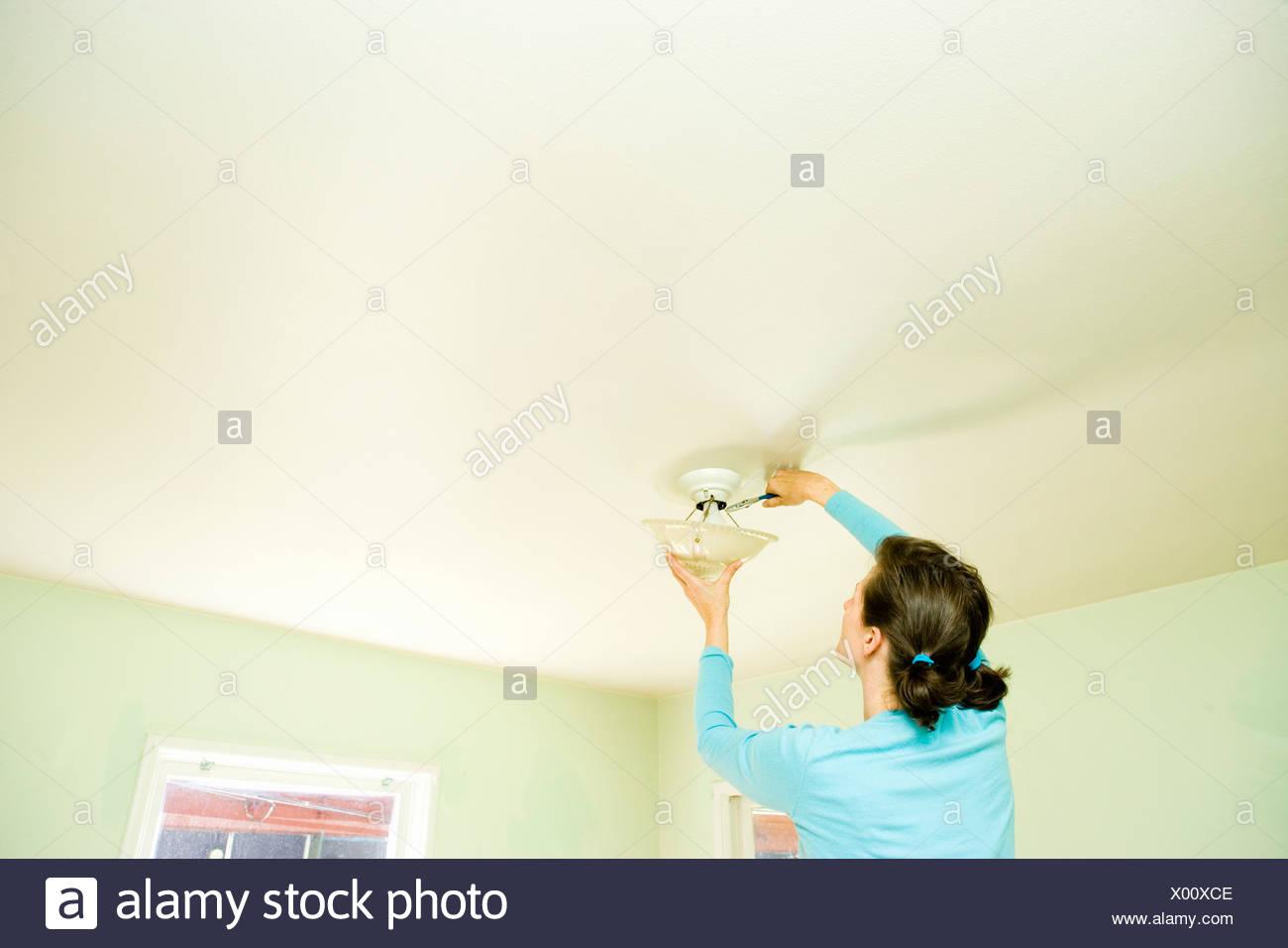 Woman Repairing Light Fixture On Ceiling