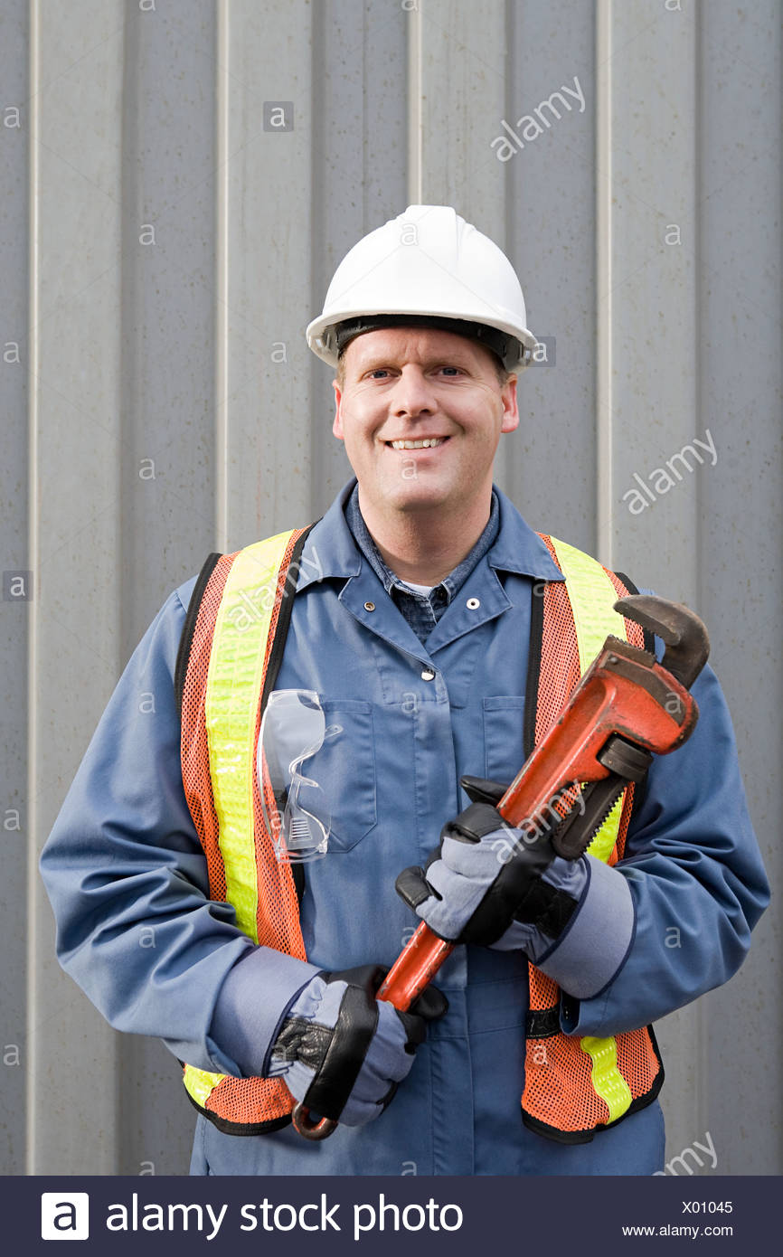 Man holding wrench - Stock Image