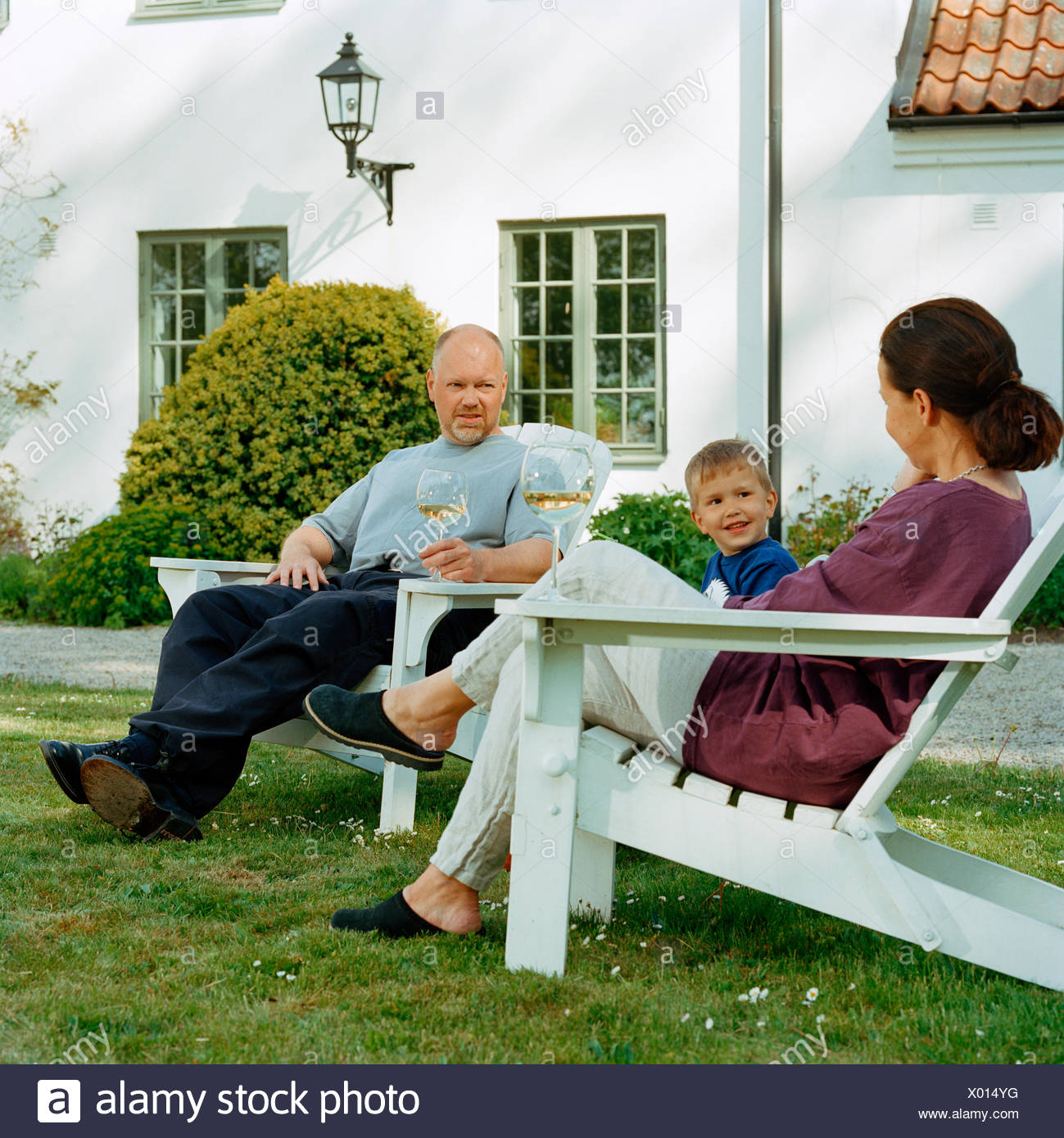 Family in a garden by a country house, Sweden. - Stock Image