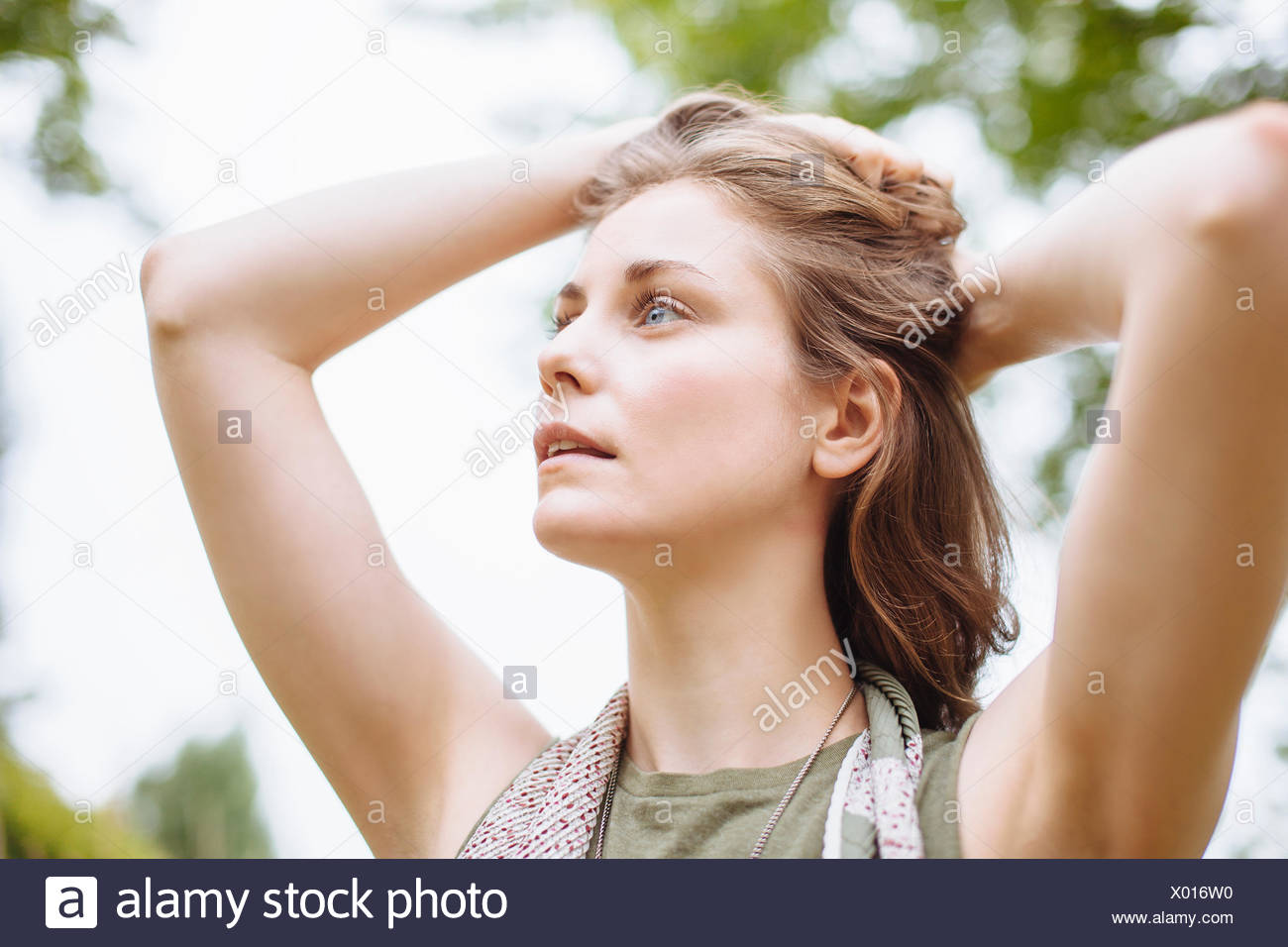 Serene young woman gazing up with hands in hair - Stock Image