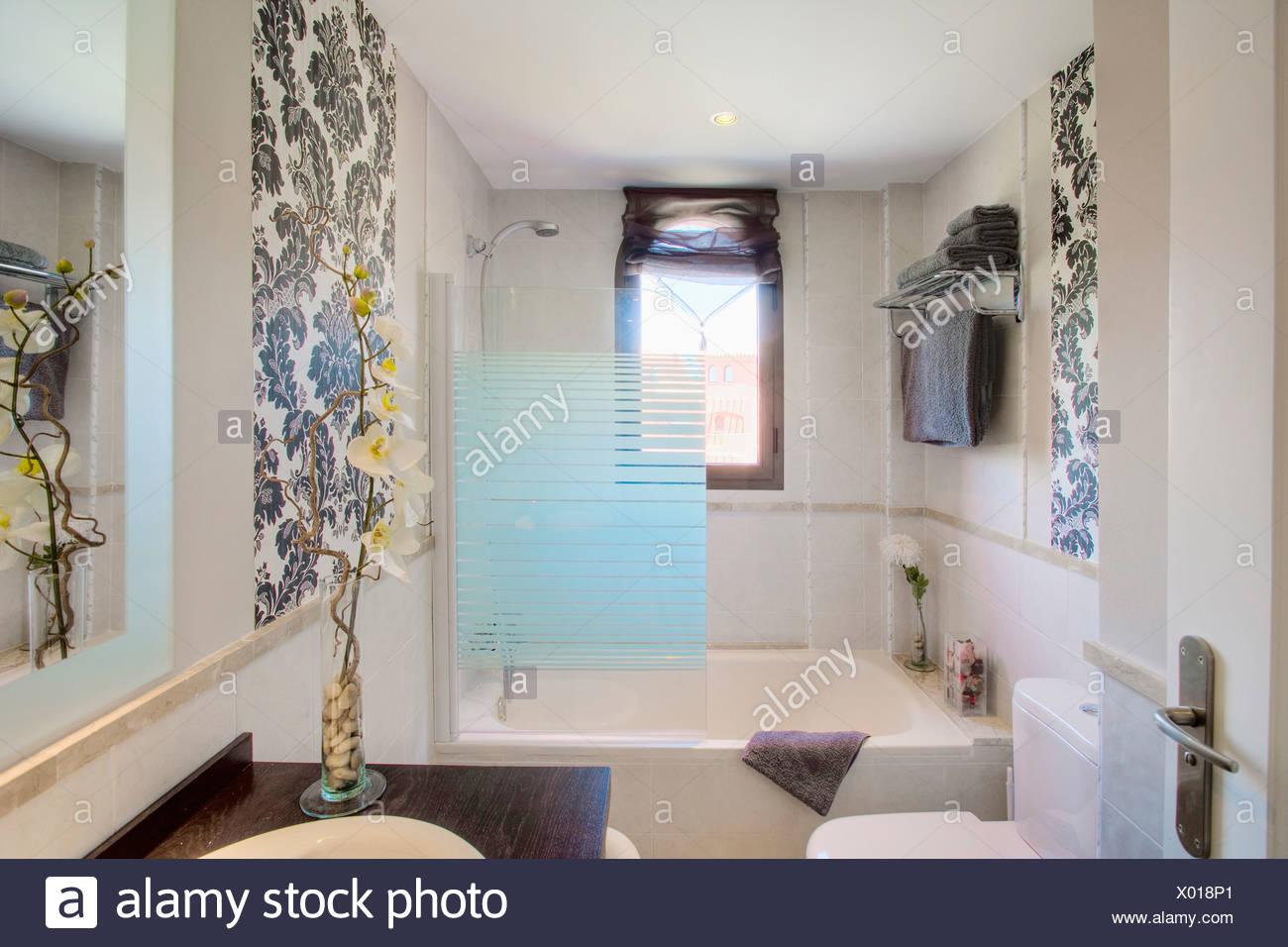 . Small modern bathroom with opaque glass shower screen on bath and