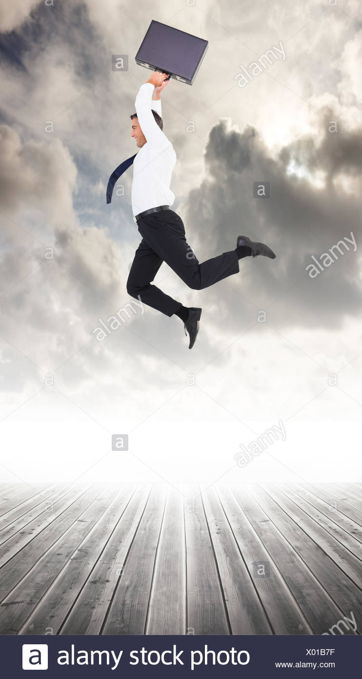 Composite image of smiling businessman leaping while briefcase - Stock Image
