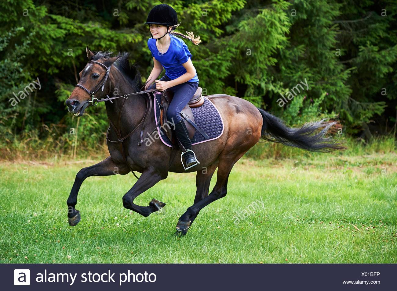 Side view of girl wearing riding hat galloping on horseback - Stock Image