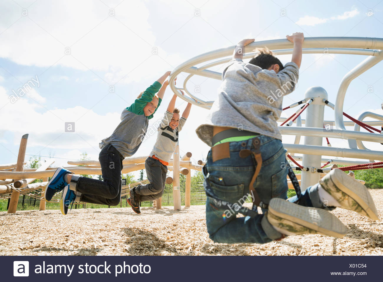 Kids hanging from swinging bar at sunny playground - Stock Image
