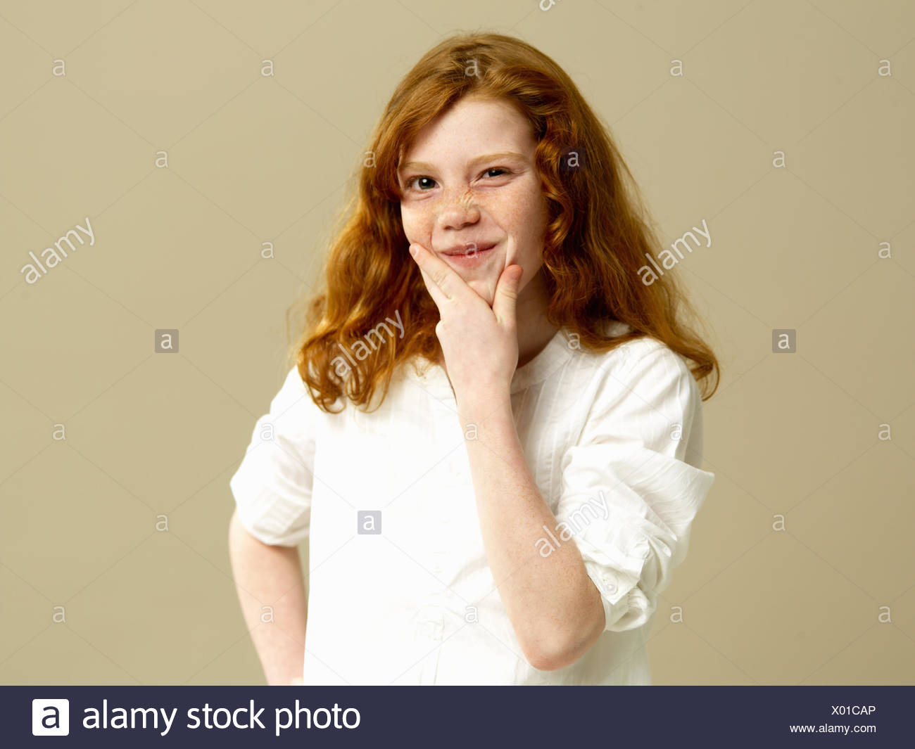 Girls, red-haired, gesture, thoughtfully, portrait, child, long-haired, blouse, shirt, freckles, hand, chin, brood, doubt undecided, think, consider, tricky, facial play, grimace, young persons, youth, childhood, studio, - Stock Image