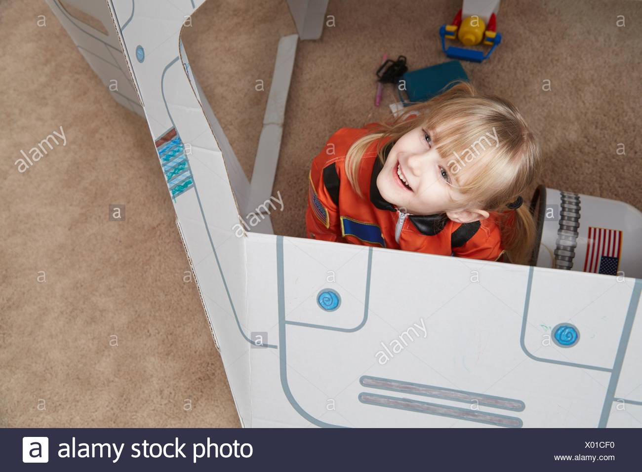 Young girl playing in cardboard spaceship, wearing astronaut outfit, elevated view - Stock Image
