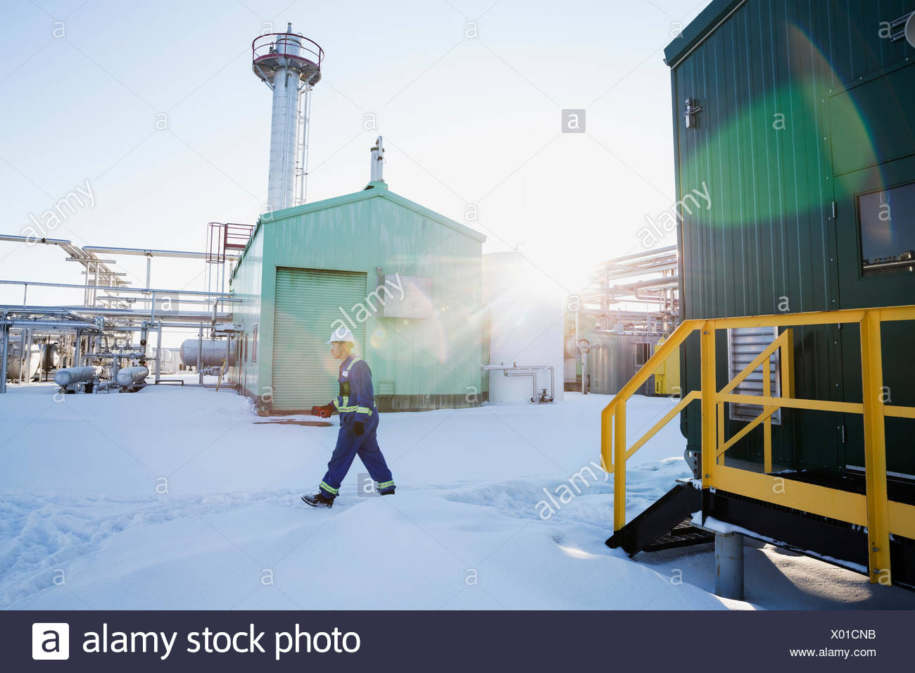 Male worker walking in snow at gas plant - Stock Image