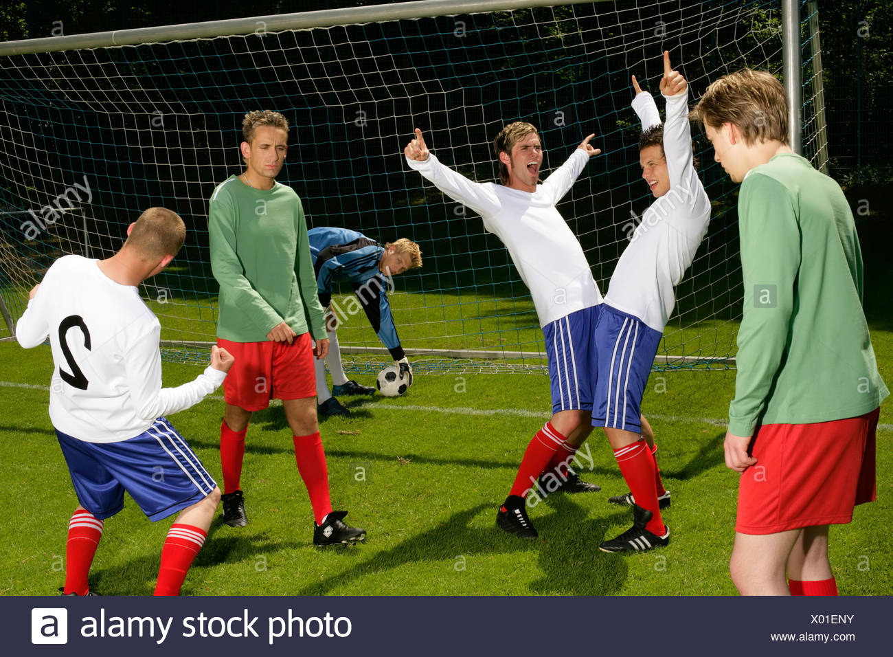 Three young footballers are happy about having won a game whereas the other team is looking sad - Stock Image