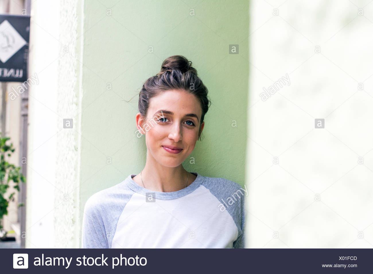 Portrait of smiling young woman with hairbun - Stock Image