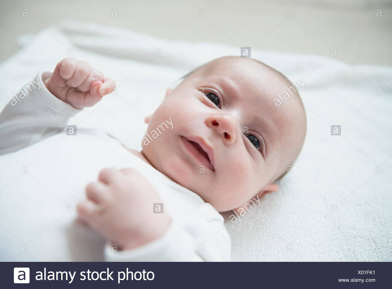 Baby boy playing on bed - Stock Image