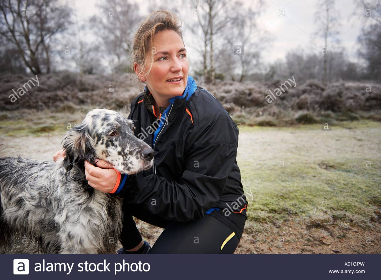 Mature woman crouching down stroking dog looking away - Stock Image