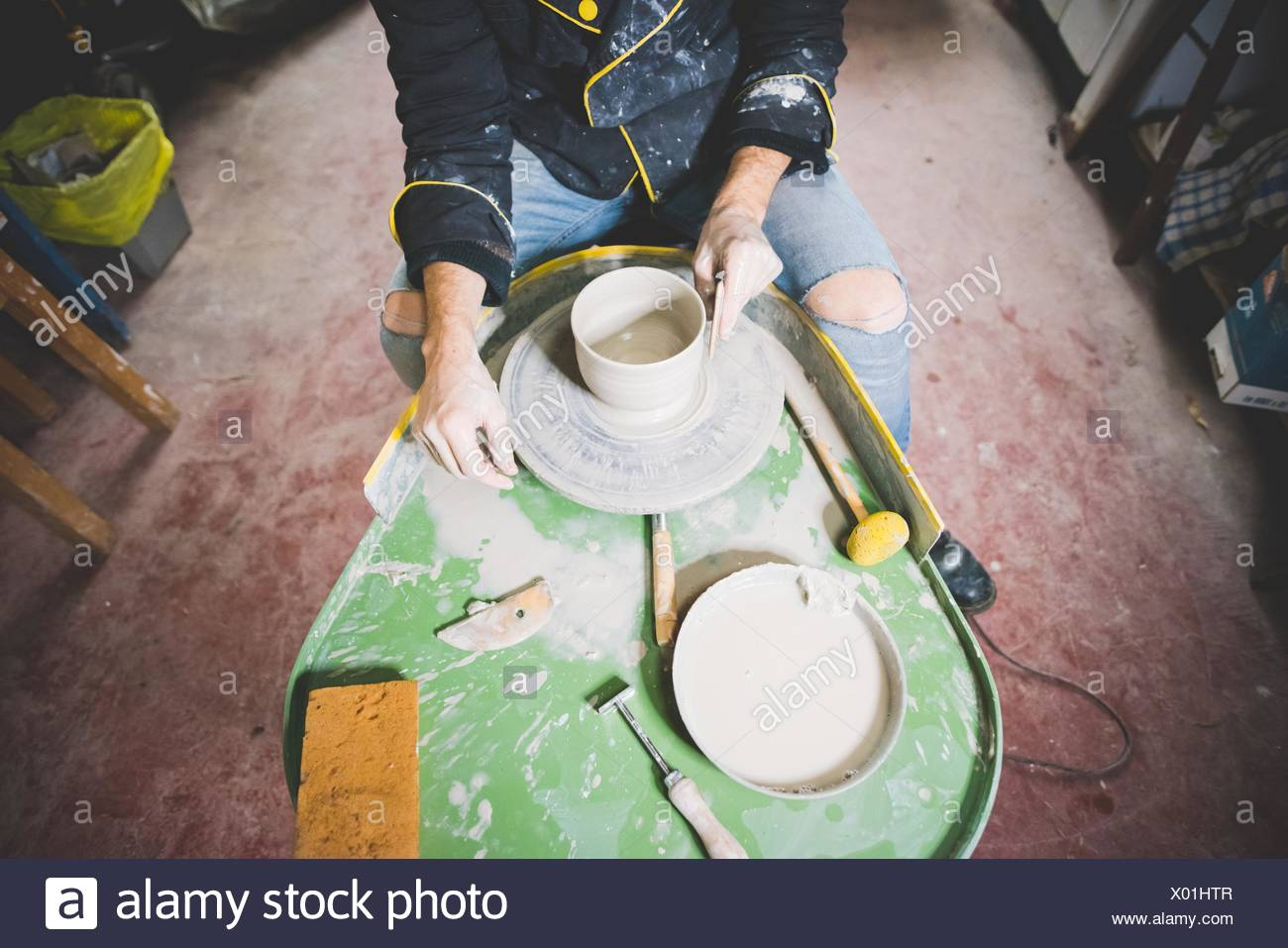 High angle view of mid adult man making clay pot on pottery wheel - Stock Image