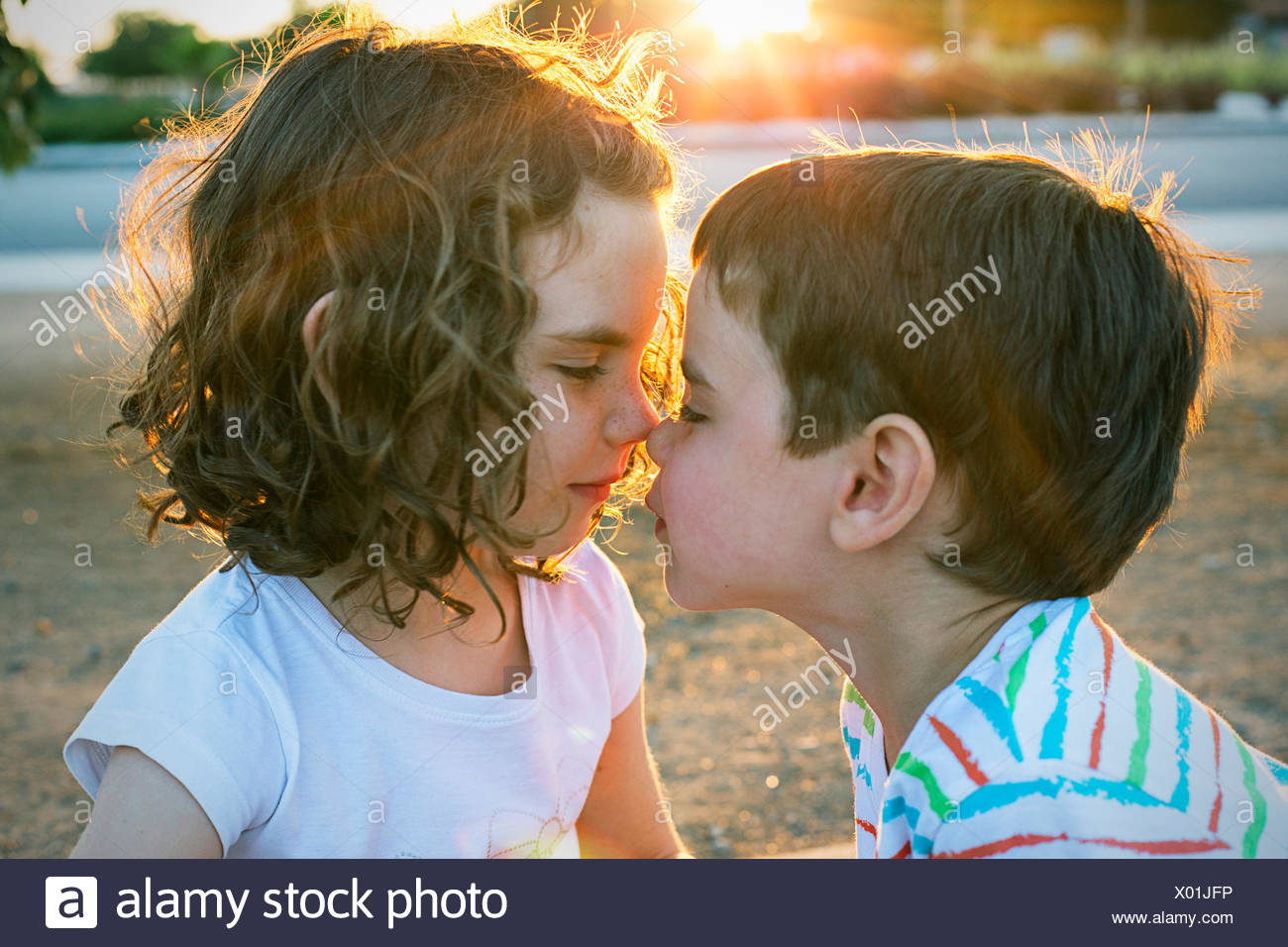 Two children rubbing noses - Stock Image