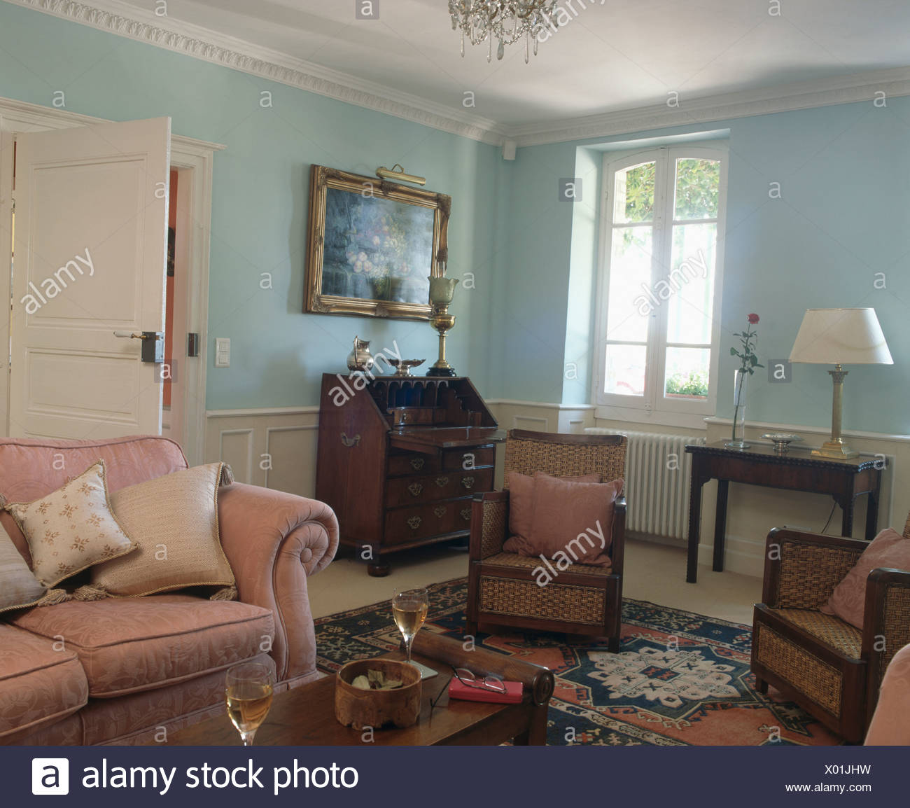 Pink sofa and English antique furniture in pastel blue ...