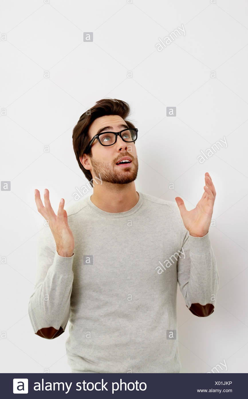 Portrait of surprised young man looking up in front of white background - Stock Image