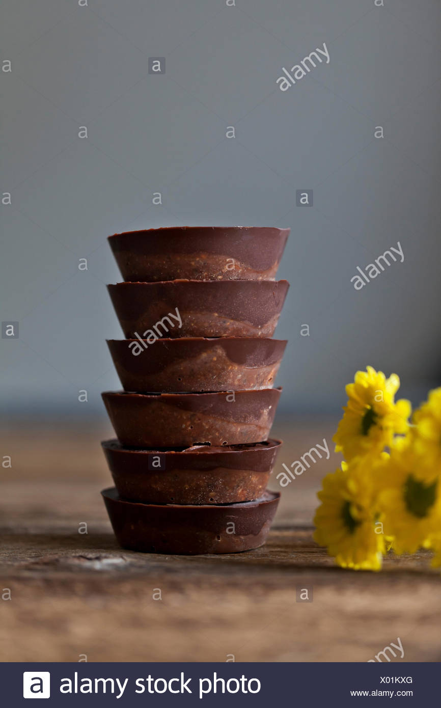 Stack of vegan date chocolate cups - Stock Image