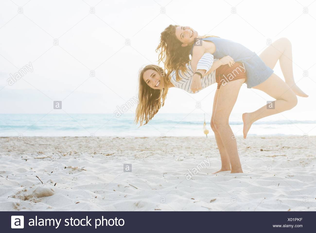 Two young female friends giving back to back lifts on beach - Stock Image