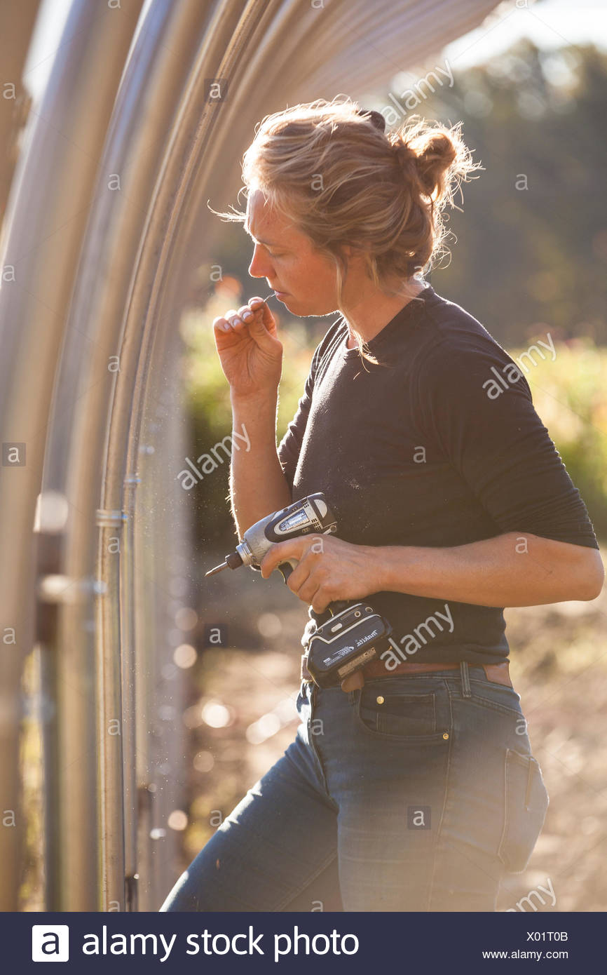 A Farmer Takes A Screw Out Of Her Mouth As She Assembles A