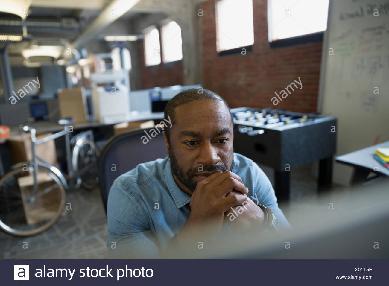 Serious entrepreneur working at computer in new office - Stock Image