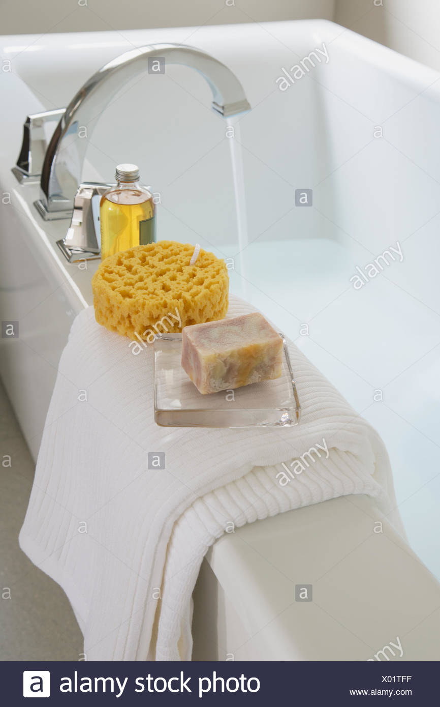 Close-up on white bath tub with bath products. - Stock Image
