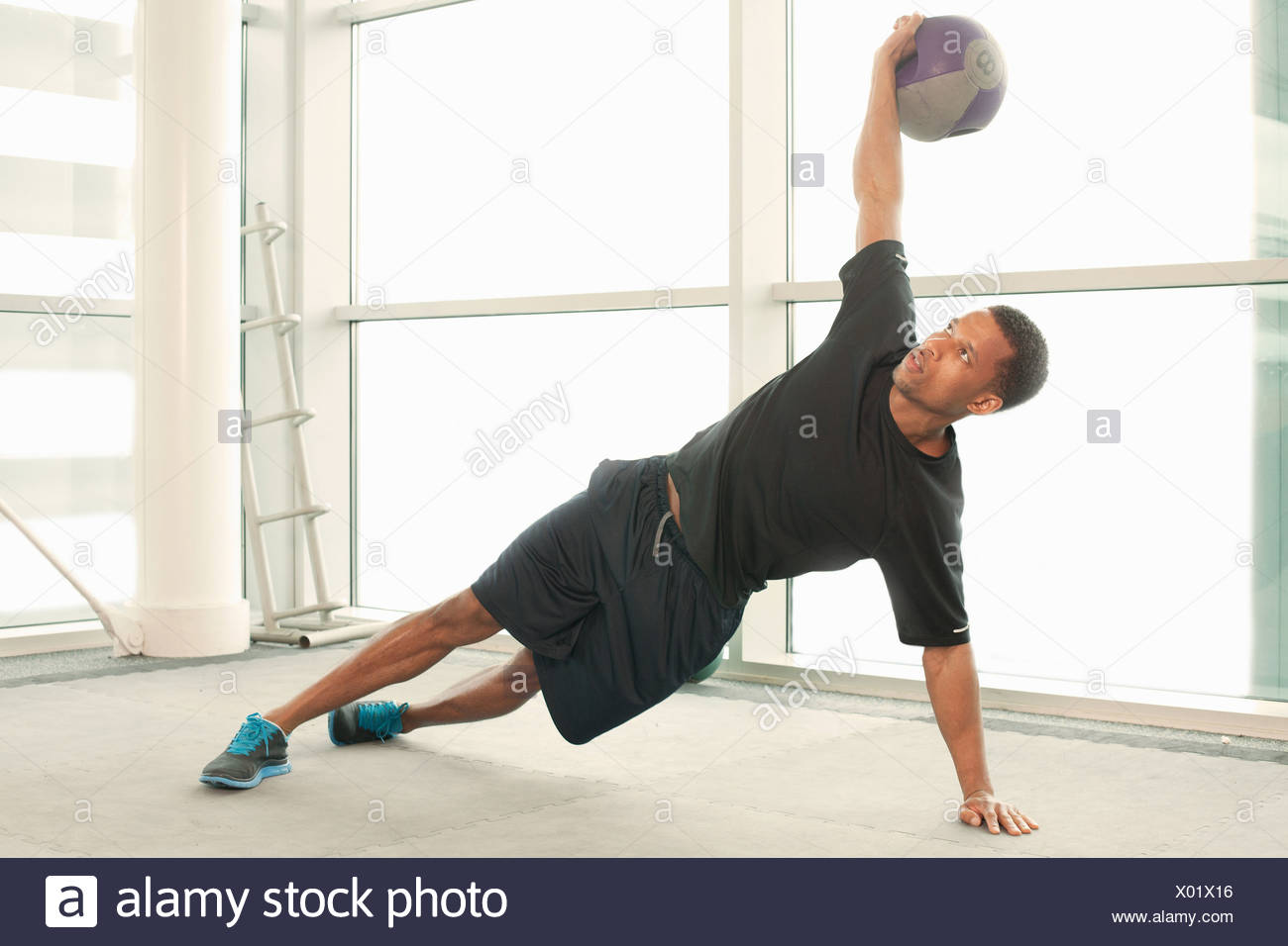 Man stretching using exercise ball - Stock Image