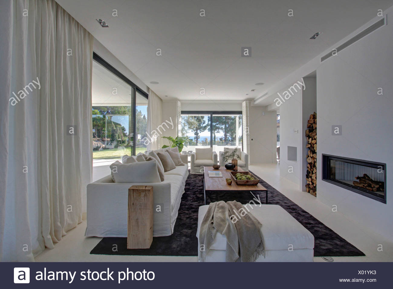 White Drapes On Large Windows In Modern White Living Room With White Sofa And Stool And Gray Carpet Stock Photo Alamy