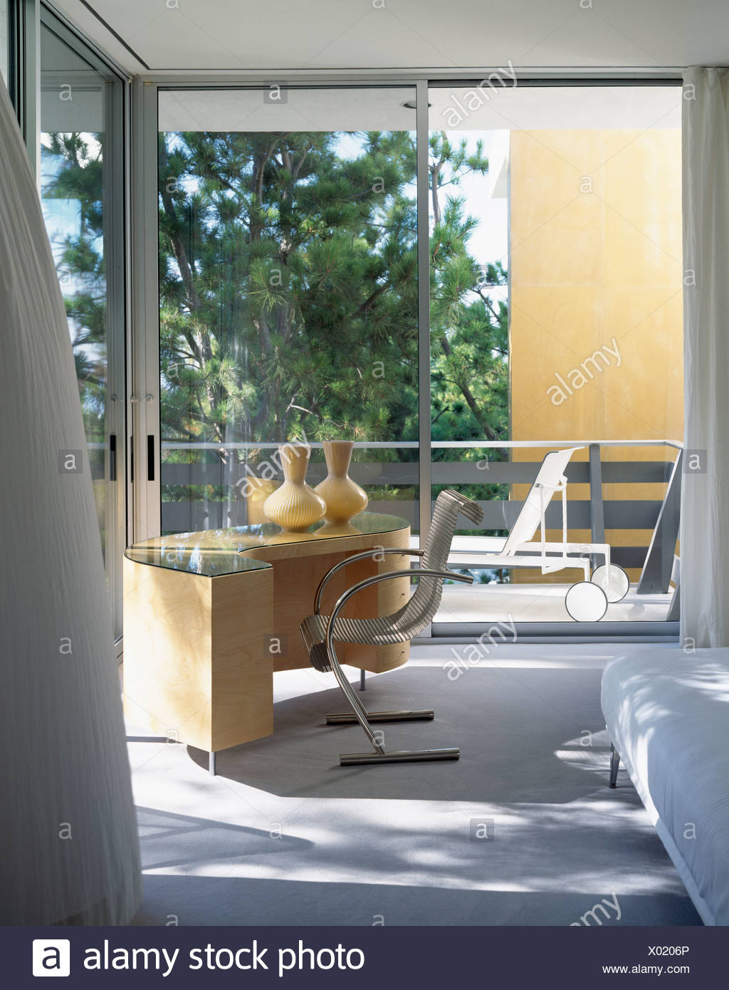 Mid Century Modern Desk And Chair In Modern Bedroom With Glass Doors Stock Photo Alamy