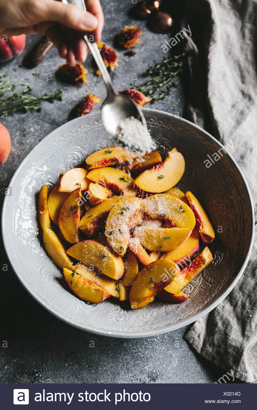A woman is sprinkling sugar over sliced peaches. - Stock Image