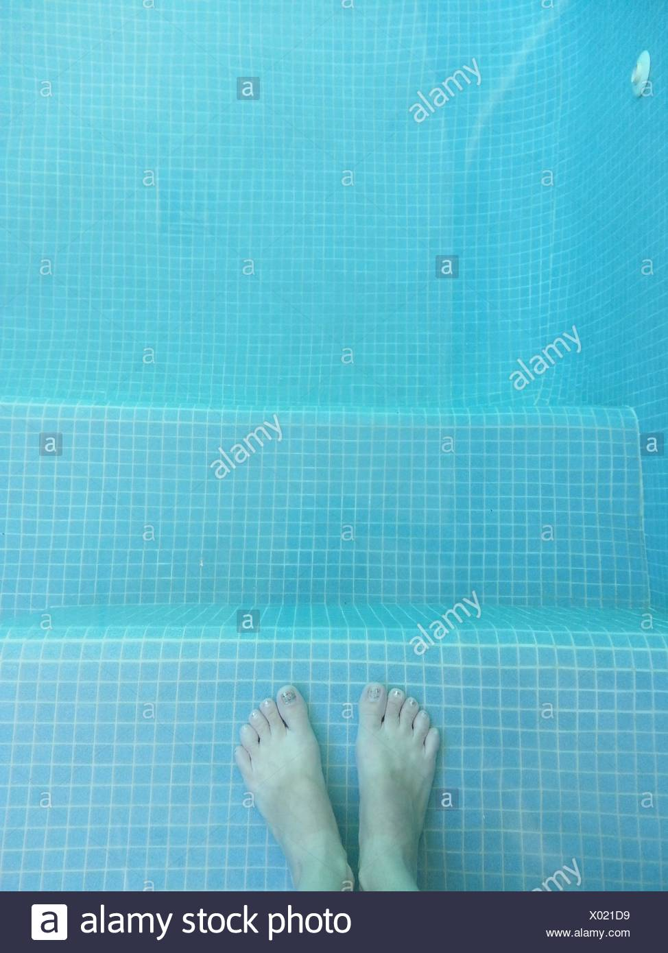 Boy's feet in swimming pool - Stock Image