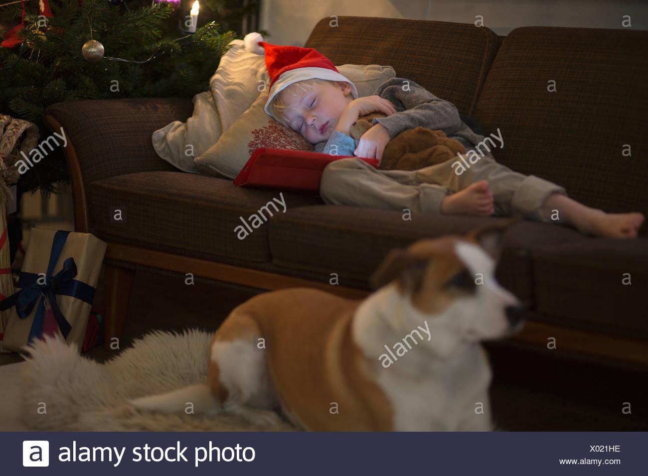 Boy in Santa hat sleeping on sofa - Stock Image