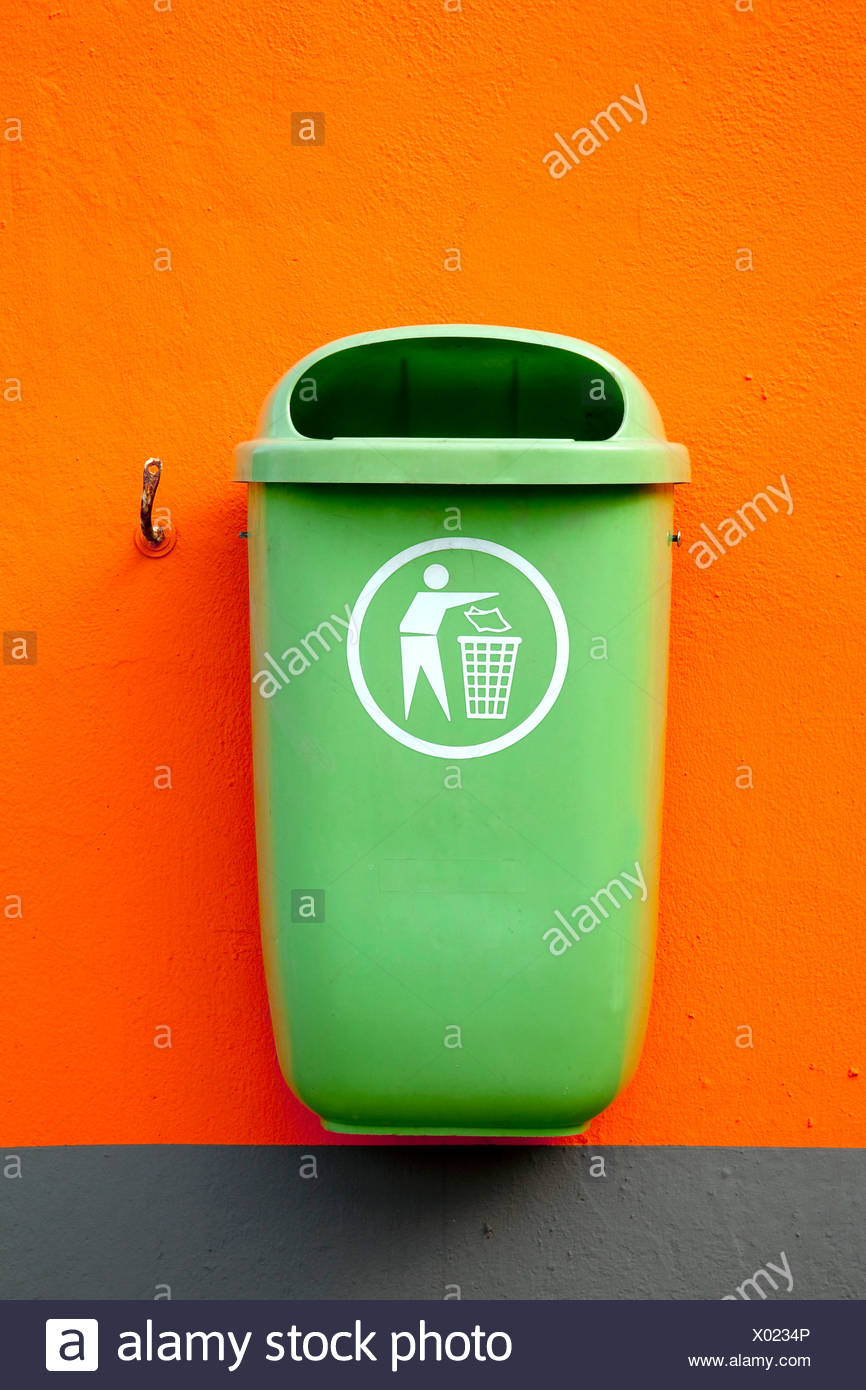 Green trash can on an orange wall in Neutraubling, Bavaria, Germany, Europe - Stock Image
