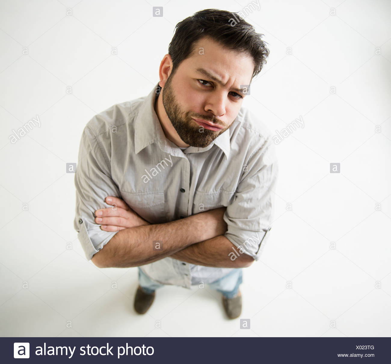 Elevated view of irritated man, arms crossed - Stock Image