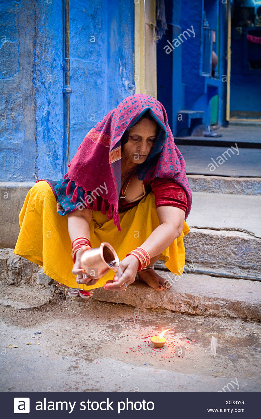 Jodhpur, India; Woman crouched over candle holding jug - Stock Image