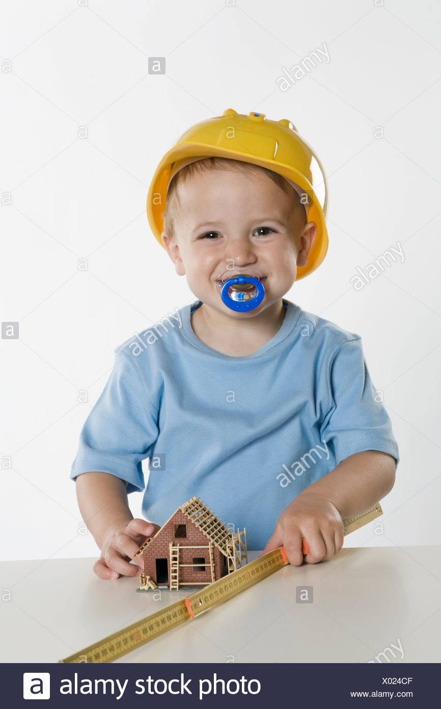 Boy (2-3) wearing hard hat, playing with folding rule - Stock Image