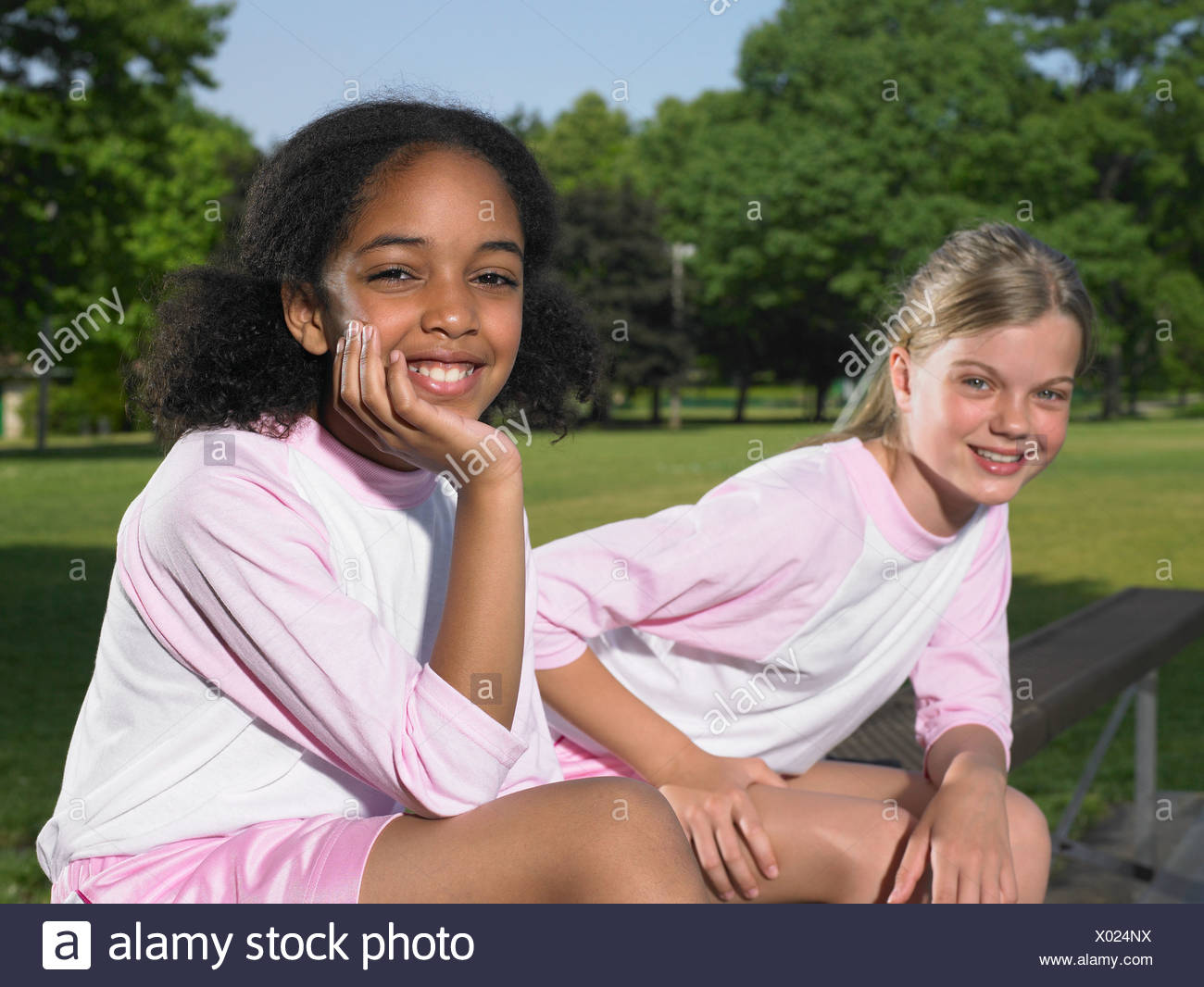 Two girls sat on a bench - Stock Image