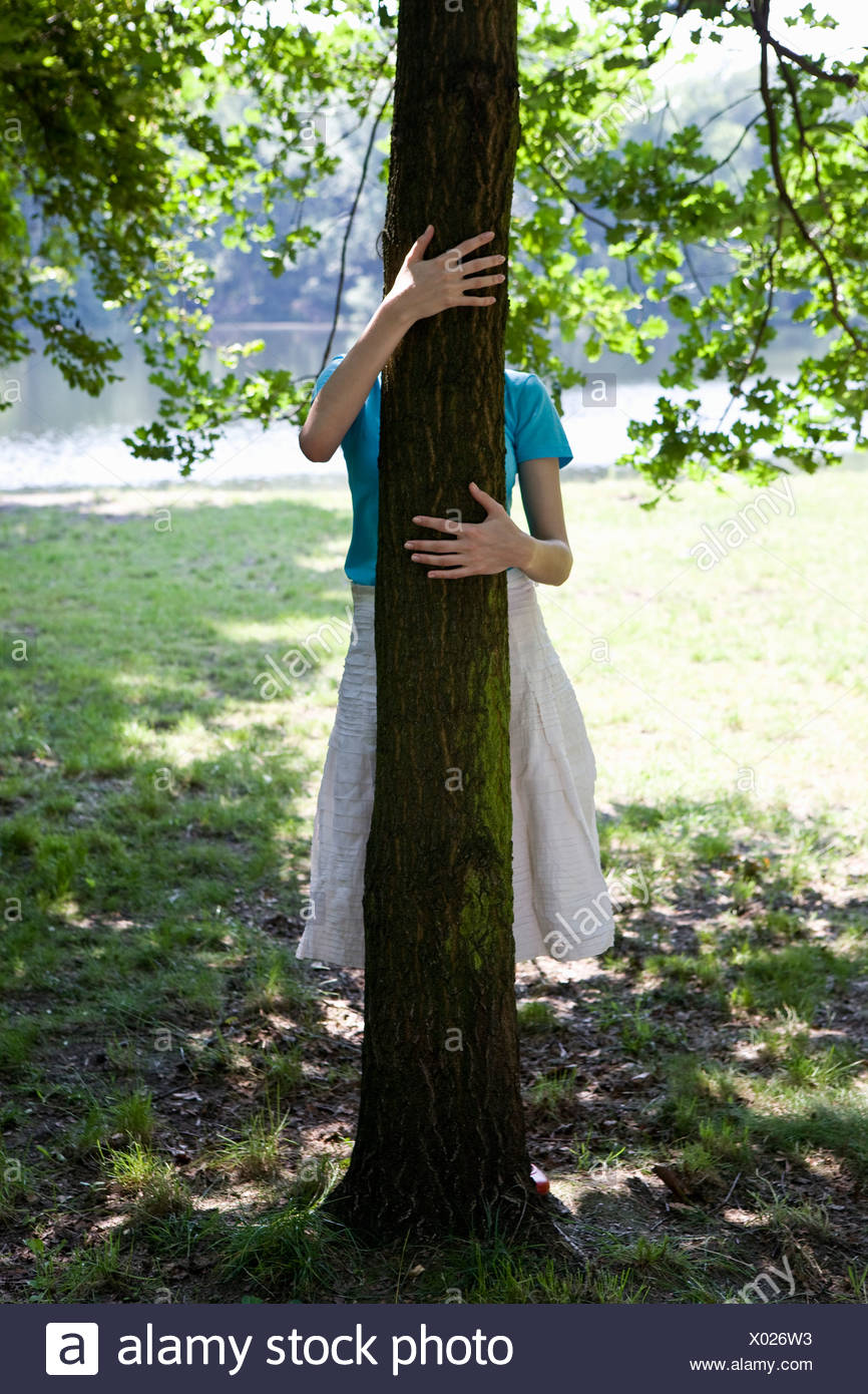 A young woman hugging a tree, obscured face - Stock Image