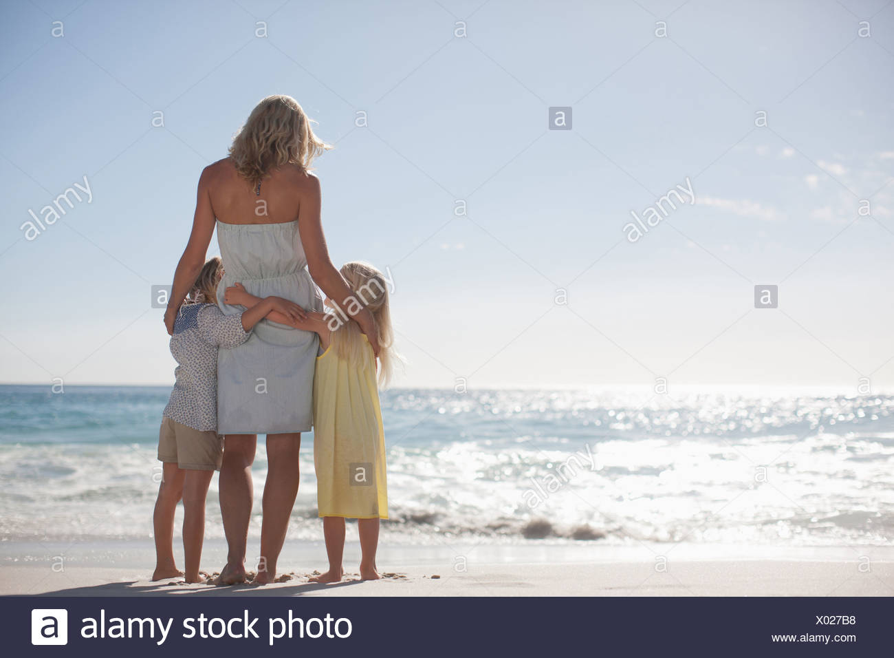 Mother and daughters on beach looking at ocean - Stock Image
