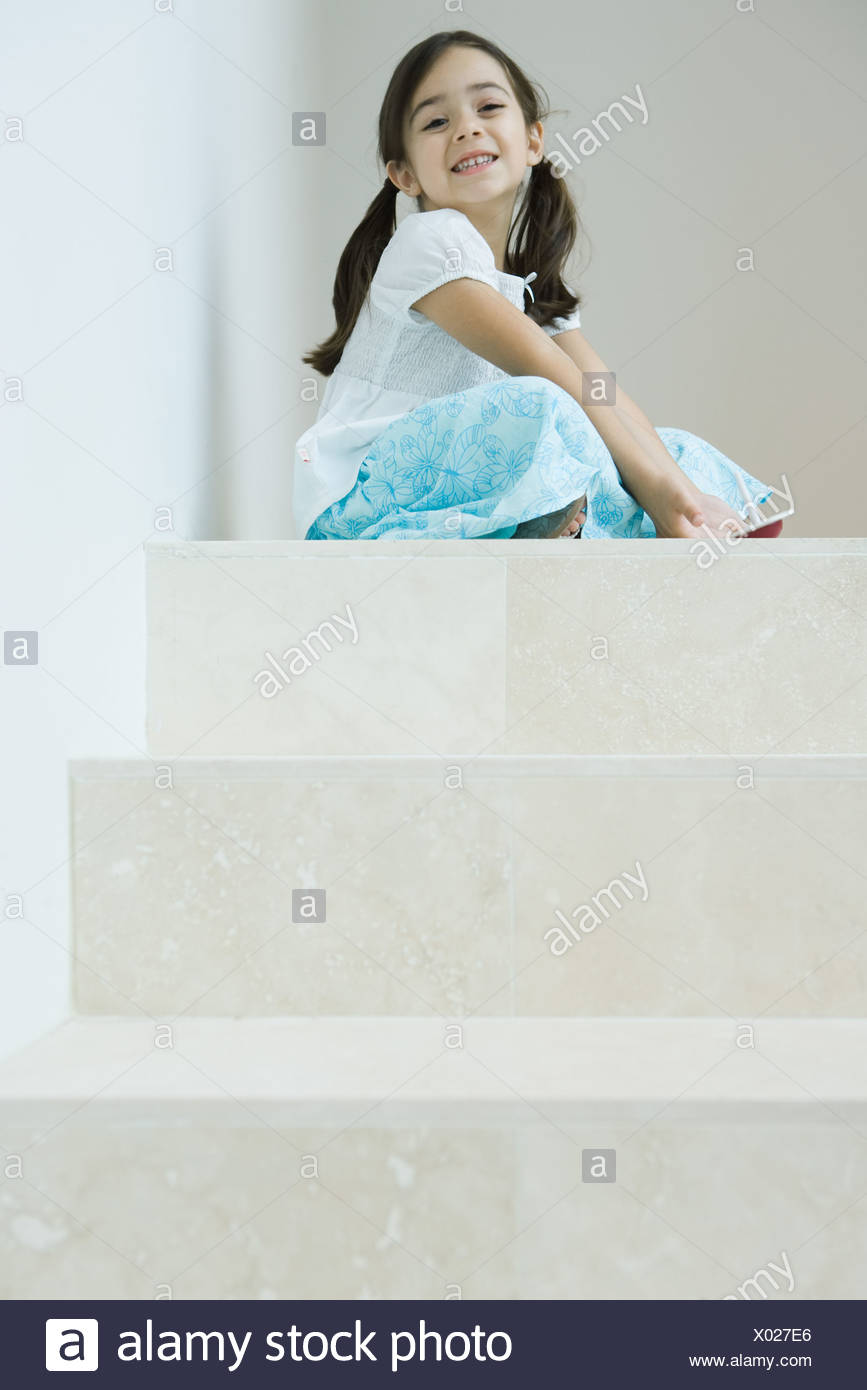 Girl sitting on steps playing with top, smiling at camera, low angle view - Stock Image