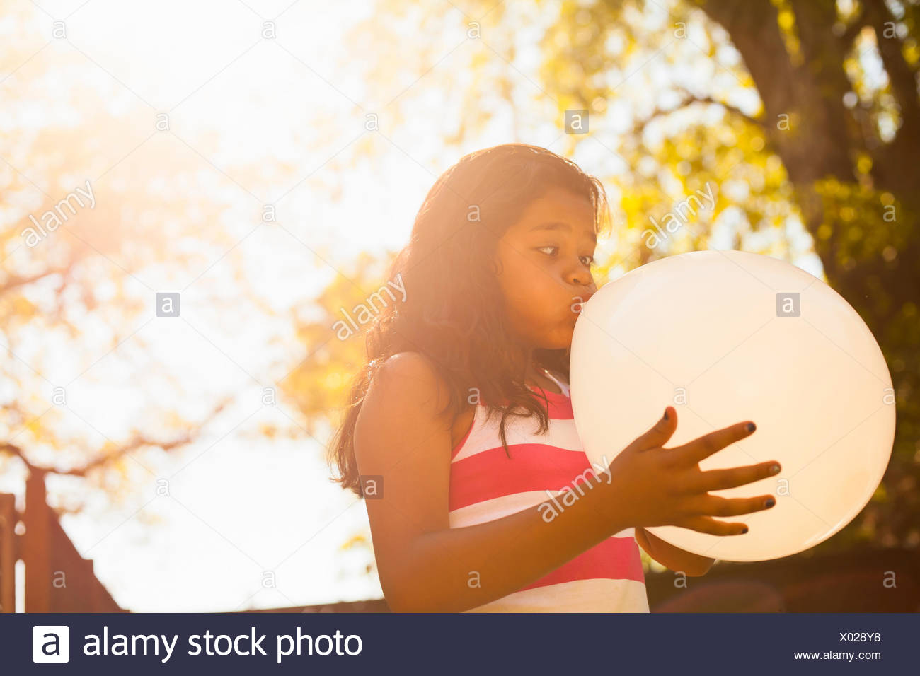 Girl blowing up balloon in garden - Stock Image
