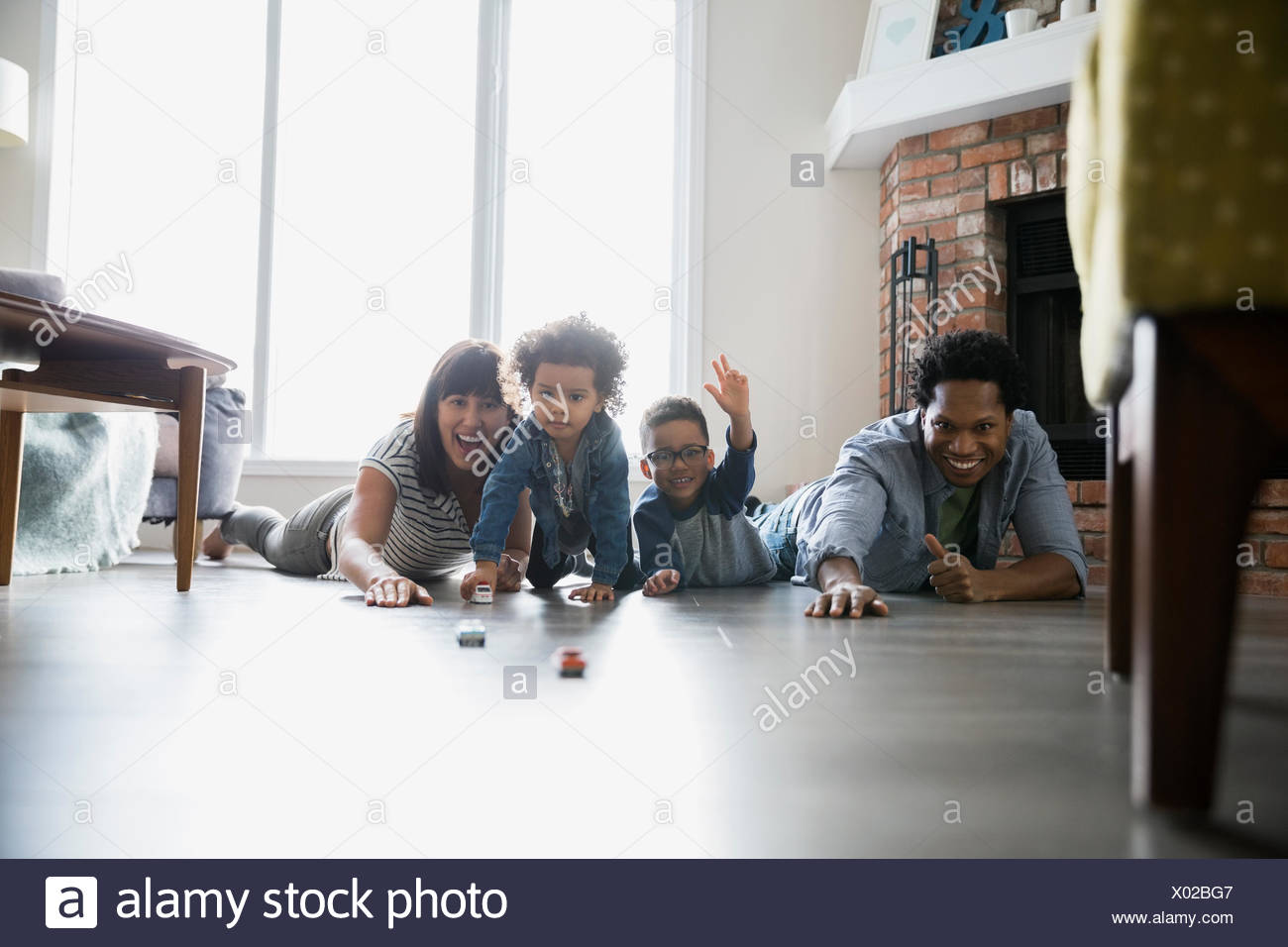 Playful family racing toy cars on floor - Stock Image
