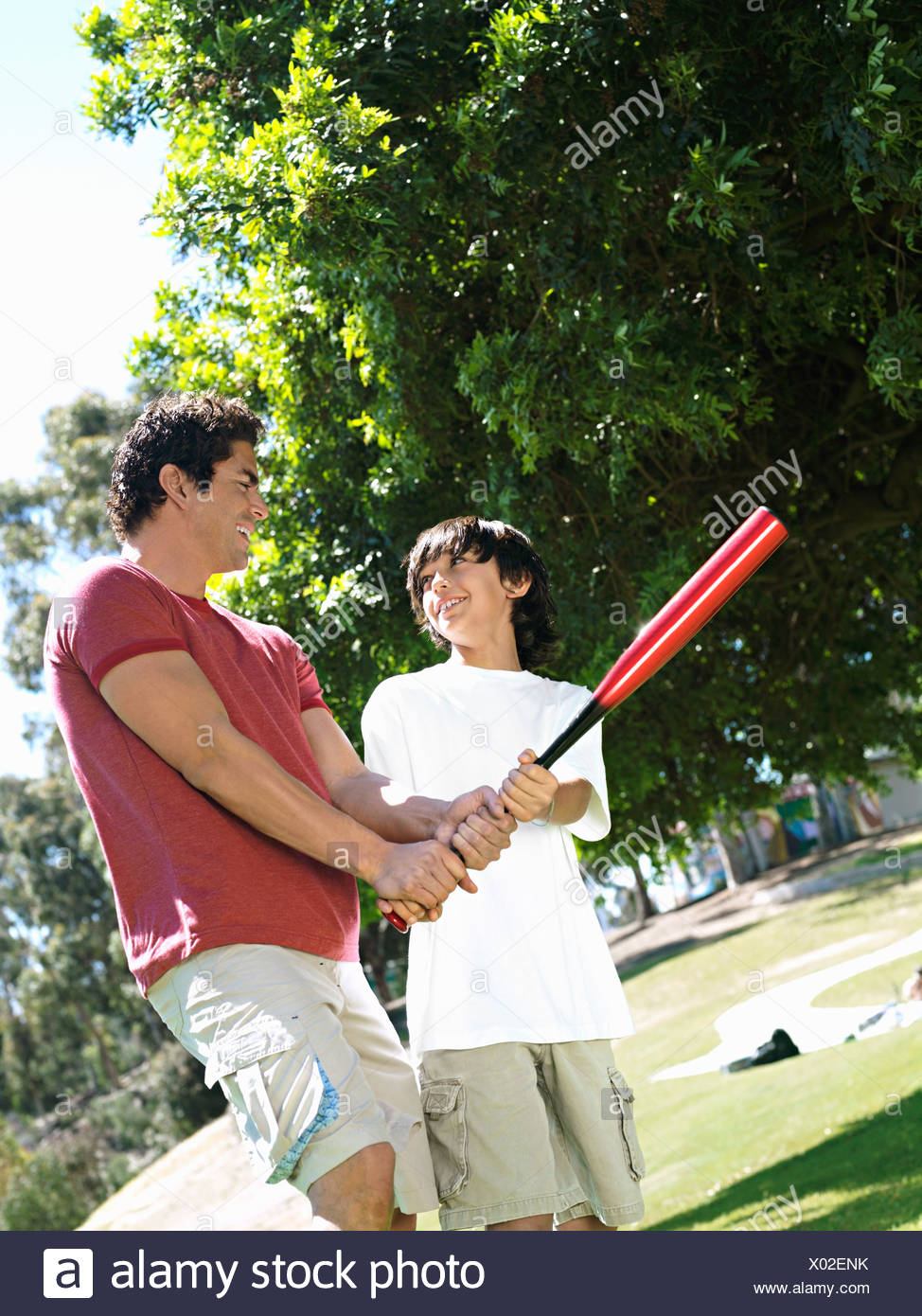 Father teaching son 10 12 how to hold baseball bat standing on grass in park smiling tilt - Stock Image