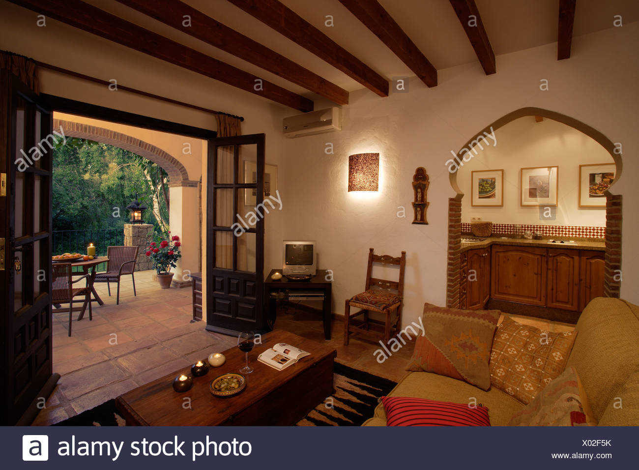 Spanish Living Room With Arched Doorway To Kitchen And Double Doors Open To  Veranda
